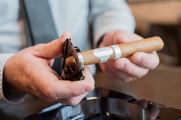 A man learning how to cut a cigar with a straight cutter at Chaloner's Cigar House in Adrian, MI.
