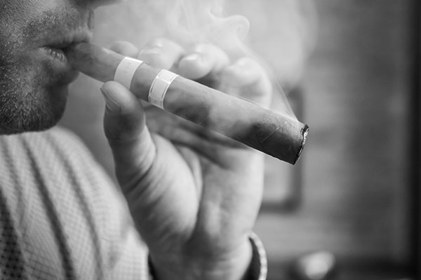A man smoking a cigar at Chaloner's Cigar House in Adrian, MI.